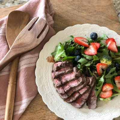 Grilled Steak over a berry field green salad