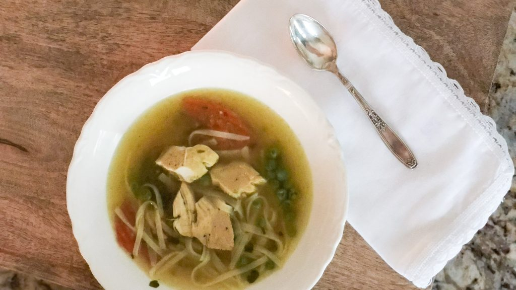 Gluten free chicken noodle soup in bowl with spoon