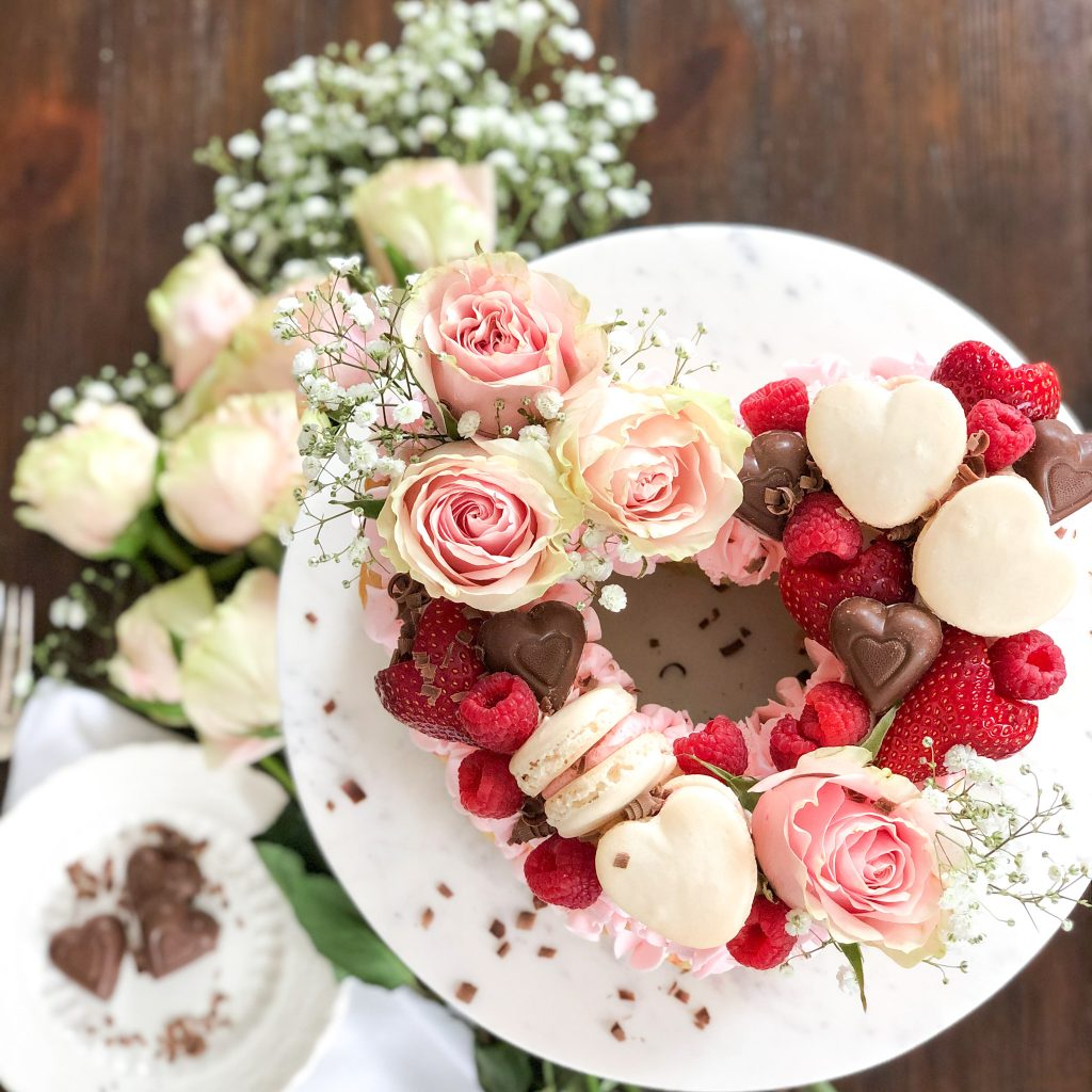 Heart shape cake with chocolates, roses, and strawberries