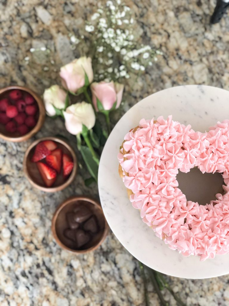 Heart shaped cake with roses, fruit and chocolates