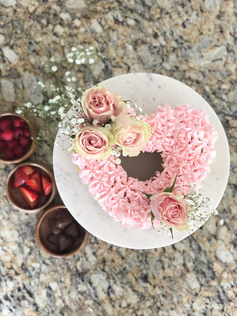 Pink Heart shaped cake with roses and baby's breath flowers