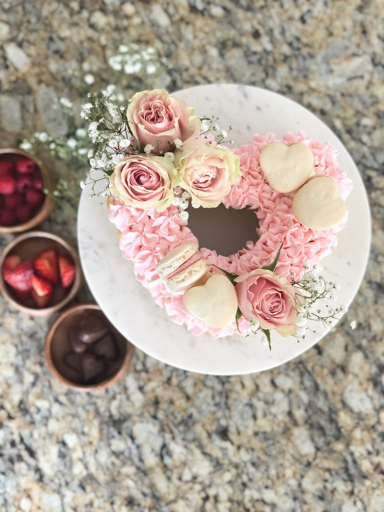 Cookies and flowers on top of a pink cake